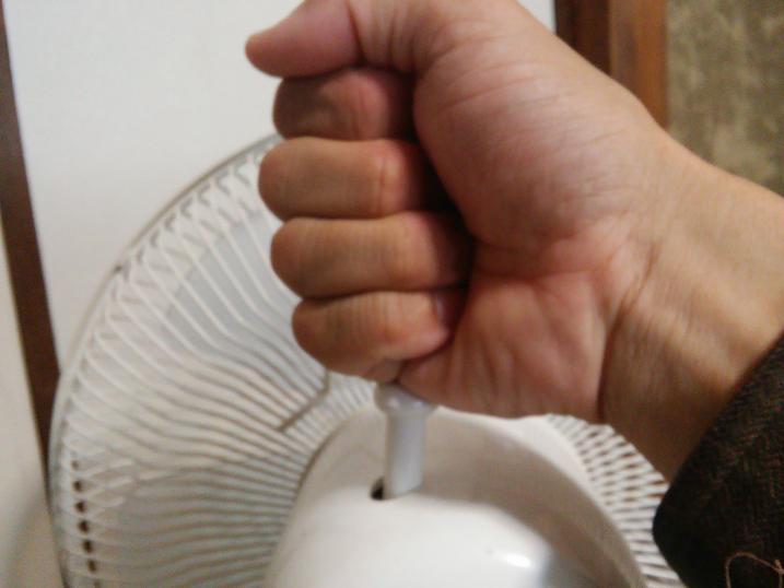 扇風機の首振りつまみを上から叩く