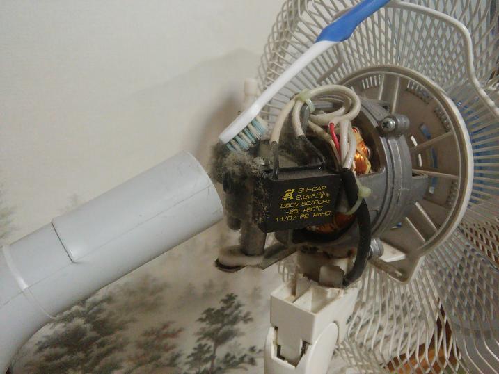 扇風機のモーター周辺のホコリを掃除機で吸い取る